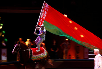 "An artist performs with a horse as he carries a Belarusian flag during the presentation of the new show ""Circuses of the world"" at the Belarus State Circus in Minsk"