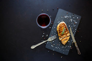 Grilled chicken fillets on slate plate with rosemary, wine and spices on dark wooden background. Top view. Flat lay. Copy space