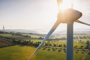 Wind turbine and agricultural fields on a summer day - Energy Production with clean and Renewable Energy - aerial shot
