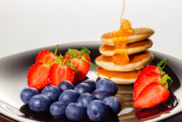 Healthy pancakes with strawberries and blueberries breakfast