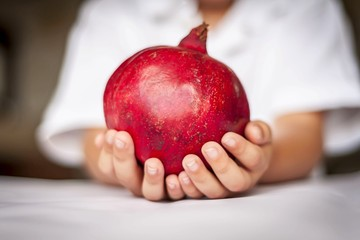 "Hands of a Caucasian child holding a pomegranate fruit. Jewish New Year ""Rosh Hashanah"" concept image. Pomegranate is a traditional symbol of this holiday."