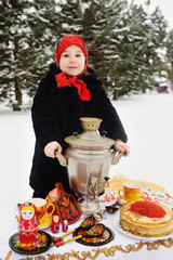 child girl in a fur coat and in a scarf in Russian style holding a large samovar in the hands of pancakes with red caviar, matryoshkas and utensils in Khokhloma style. Maslenitsa, Russia, winter