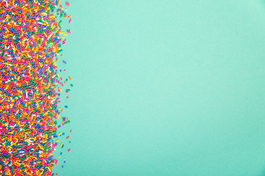 Colorful sprinkles on edge of green background