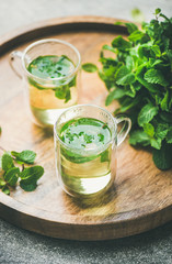 Hot herbal mint tea drink in glass mugs over wooden tray with fresh garden mint leaves, selective focus, vertical composition
