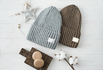 Knitted hats, cotton sprigs, macaroons close-up on a white