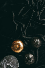 top view of decorative black and golden painted pumpkins on black cloth for traditional halloween party