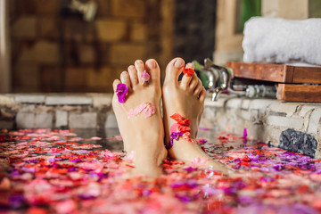 Attractive Young woman in bath with petals of tropical flowers and aroma oils. Spa treatments for skin rejuvenation. Alluring woman in Spa salon. Girl relaxing in jacuzzi with flower petals.
