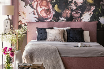 Pink and grey bed with cushions in patterned bedroom interior with flowers and lamp. Real photo