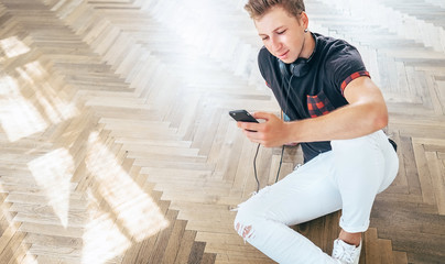 Young man using his smartphone with headphones, listen the music and sit on the floor