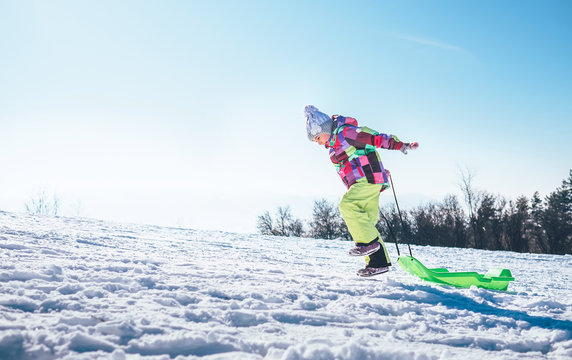 Happy little girl jumps up on the snow slope with bright plastic sleigh