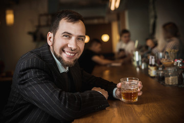 Elegant man in expensive suit near bar counter is smoking cigar and drinking whiskey
