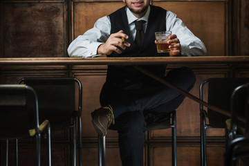 Man sits in the luxury bar in male gentlemen club and drinks alcohol