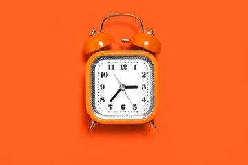Vintage style orange metal alarm clock with bells standing on the orange surface isolated. back to school concept. free space for text