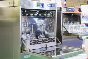 Open door of dishwasher with clean glasses by using water; food industrial equipment background