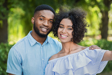 Excited black couple taking selfie at park
