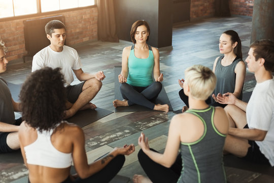 Diverse group meditating in yoga class