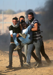 Wounded Palestinian is evacuated during a protest at the Israel-Gaza border fence, in the southern Gaza Strip