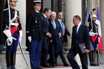French President Emmanuel Macron reacts with Palestinian President Mahmoud Abbas after a meeting at the Elysee Palace in Paris