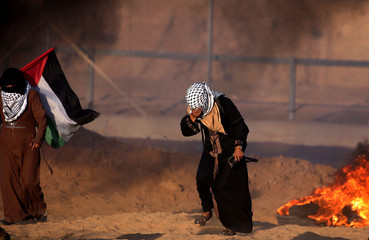 Woman reacts from tear gas during a protest of Palestinians at the Israel-Gaza border fence, in the southern Gaza Strip