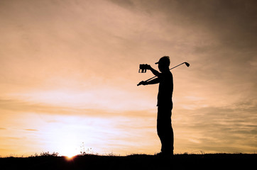 Silhouette golf athlete was photographed himself with a beautiful sky of sunset