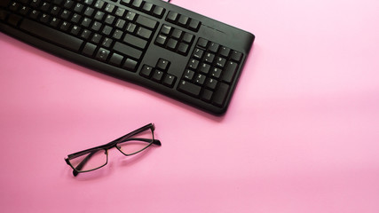 Wall Mural - Black keyboard with galsses on pink background.Business concept