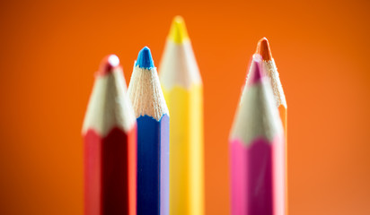 Set of multicoloured  pencil or crayon on orange background.Selective focus