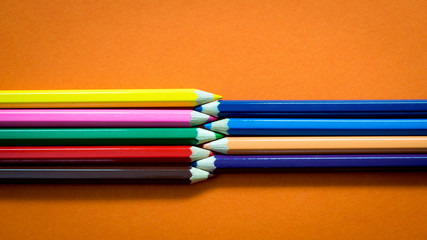 Wall Mural - Set of multicoloured  pencil or crayon on orange background.Top view