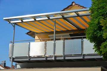 Edelstahl-Balkon mit Edelstahlrahmen-Glasdach und orange-grau gestreifterer Markise