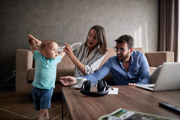 man and woman spending happy time at home with their baby son and playing together.
