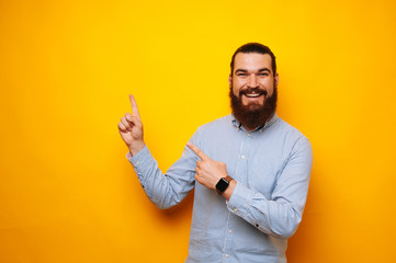 Happy cheerful young bearded man smiling and pointing at copyspace over yellow background
