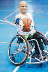 Disabled sport men in action while playing indoor basketball