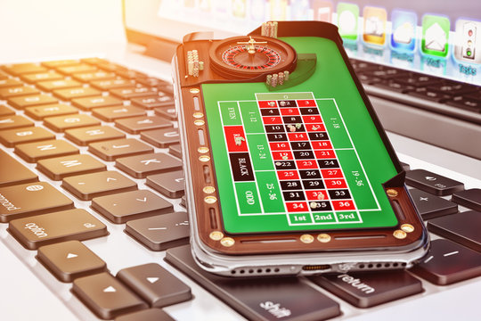 Online casino and gambling concept, mobile phone with a roulette play field on a laptop keyboard closeup