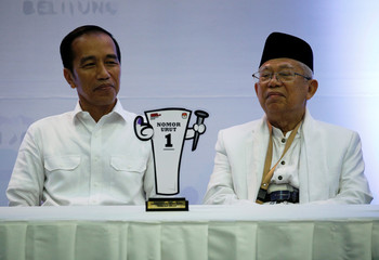 Indonesian President Joko Widodo and his running mate in next year's presidential election Islamic cleric Ma'ruf Amin attend a ceremony at the election commission headquarters in Jakarta