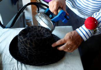Belgian hat-designer Elvis Pompilio irons a hat in his workshop in Brussels