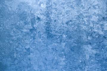 Natural blue winter frosty icy pattern on window pane.