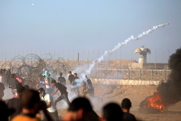 Palestinians run from tear gas during a protest at the Israel-Gaza border fence, in the southern Gaza Strip