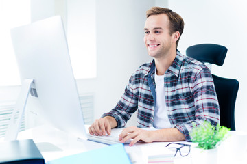 Young man in casual wear working with computer