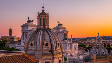 Beautiful sunset in Rome in orange, pink, purple and purple colors – a view of the landmarks and ancient architecture in the city center from the roof of the historic building