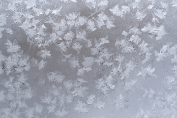 Close-up icy pattern of frozen snowflakes on window pane.
