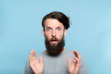 omg unbelievable shock amazement. dumbfounded man with open mouth. portrait of a young bearded guy on blue background. emotion facial expression and reaction concept.