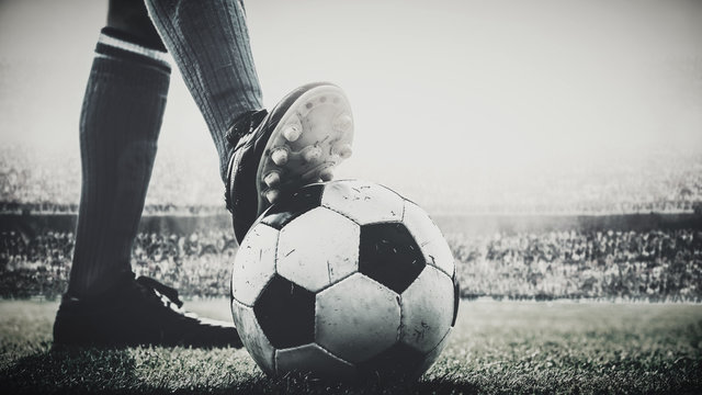 feet of soccer player tread on soccer ball for kick-off in the stadium black and white