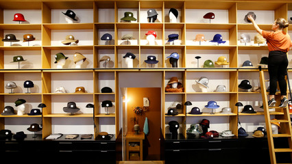 An employee of headwear manufacturer Muehlbauer puts a hat on a shelf in the company's store in Vienna