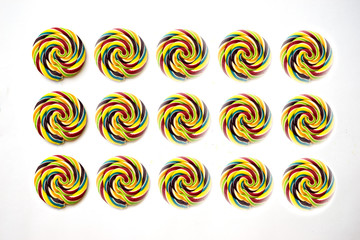 Lollipop swirl large candy on wooden stick hipster rainbow colored isolated on white background, flat lay