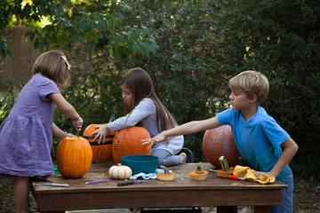 Siblings making jack-o-lanterns out of pumpkins.