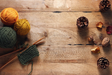 A piece of knitting with wooden needles and yarn among leaves and pine cones.
