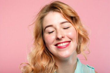emotion expression. very happy joyful thrilled to bits woman with beaming smile. young beautiful blond girl portrait on pink background.