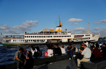 A passenger ferry arrives at Eminonu pier as people sit by the Bosphorus in Istanbul