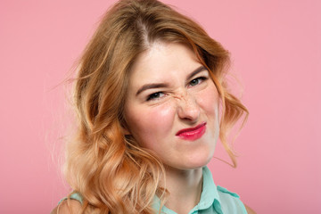 nah, not impressed. unimpressed girl grimacing and wrinkling nose. emotion expression and reaction concept. young beautiful blond girl portrait on pink background.