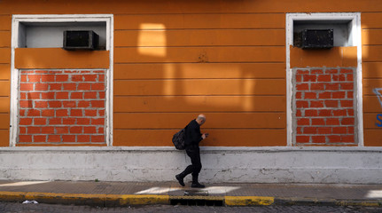 A man walks outside a house for sale that has its windows sealed with bricks to prevent it from being illegally occupied in Buenos Aires