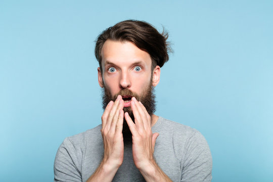 omg unbelievable shock amazement. astounded man with open mouth. portrait of a young bearded guy on blue background. emotion facial expression and reaction concept.